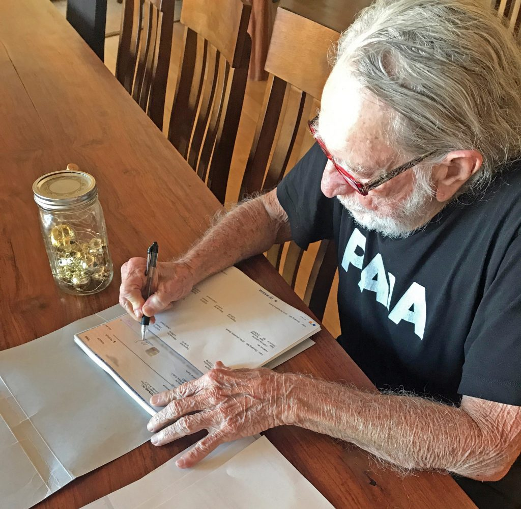 Willie Nelson signing Farm Aid 2019 grant checks